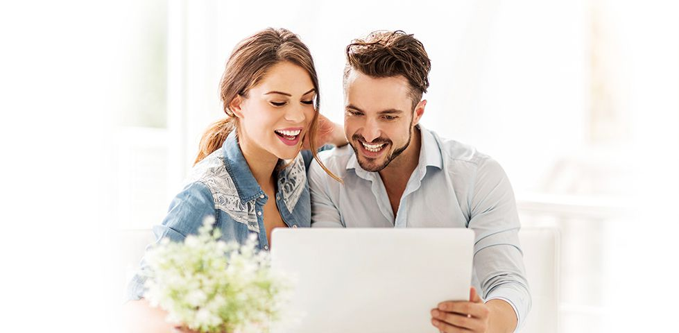 man and woman smiling behind a laptop