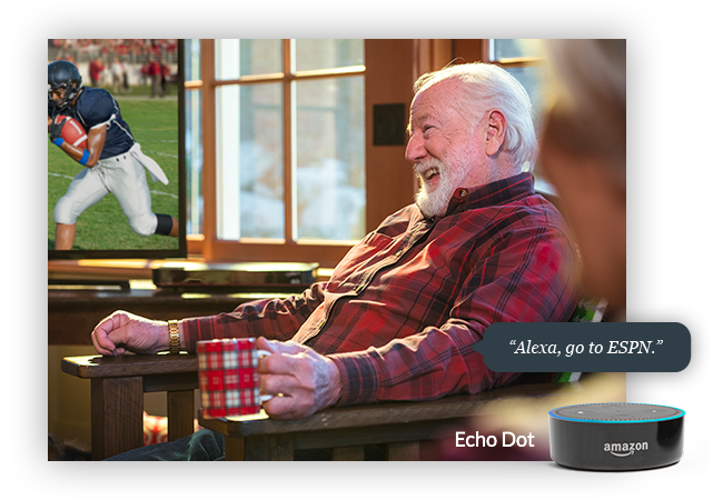Man in armchair, with an Amazon Echo Dot receiving the command 'Alexa, go to ESPN'