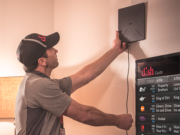 DISH Technician mounting an over-the-air antenna next to a TV